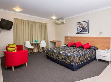 king deluxe bedroom with two mini dining ,coffee table and couches by nambour heights motel