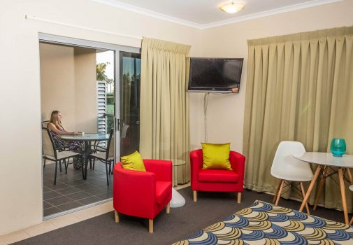 king deluxe bedroom with two mini dining ,coffee table, couches, and balcony by nambour heights motel