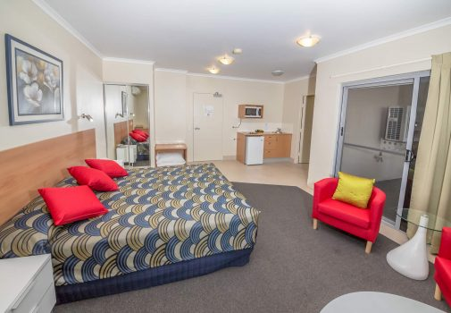 king deluxe bedroom with mini kitchen, closet, coffee table and spare pillow by nambour heights motel